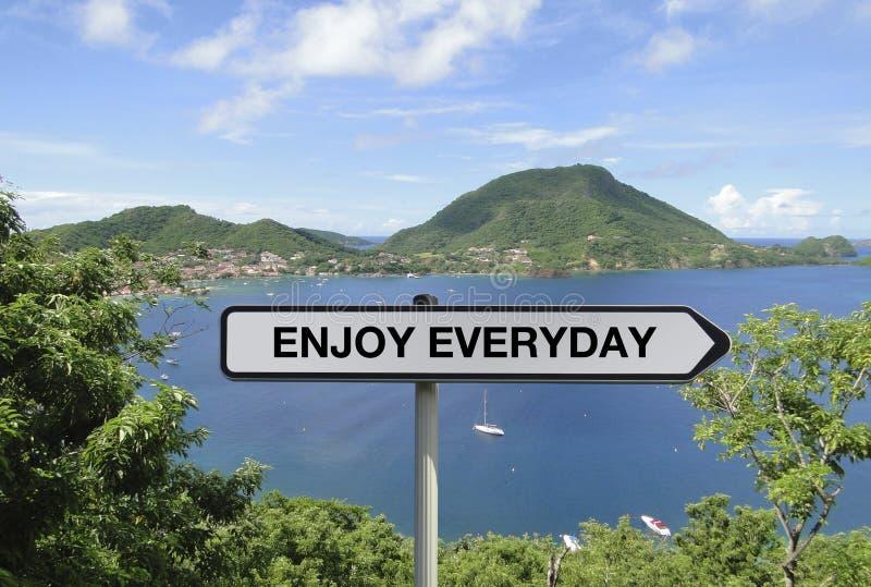 Straßenschild mit ENJOY JEDEN TAG Text unter tropischem Inselhintergrund stockfotos