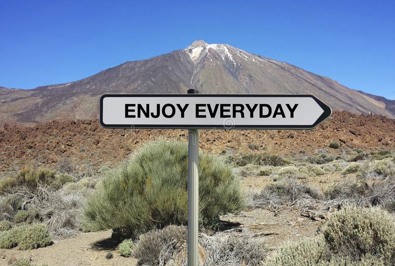 Straßenschild mit ENJOY JEDEN TAG Text unter vulkanischem Hintergrund lizenzfreies stockfoto