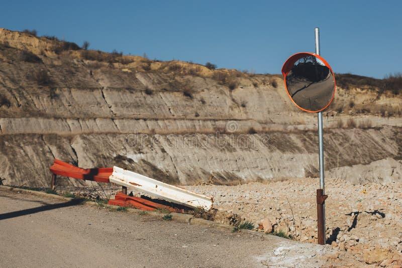 Straßenspiegel nahe bei einem Steinsteinbruch stockfoto