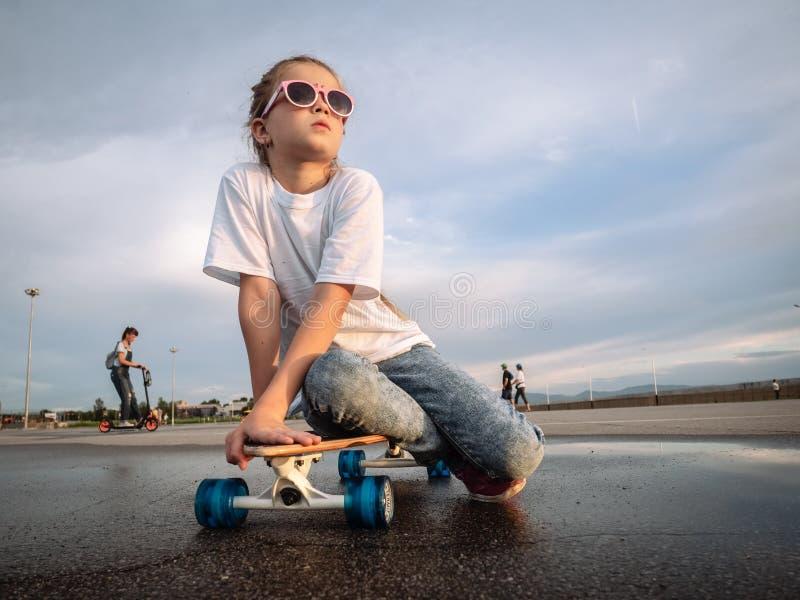Straßensport: Jolly Girl in der Sonnenbrille setzte sich hin, um sich auf dem longboard nach einem Weg im Park für den Eislauf zu stockfotos