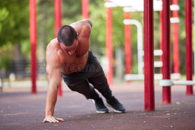 Straßentraining - hübsches muskulöses Manntraining im Park stockfotos