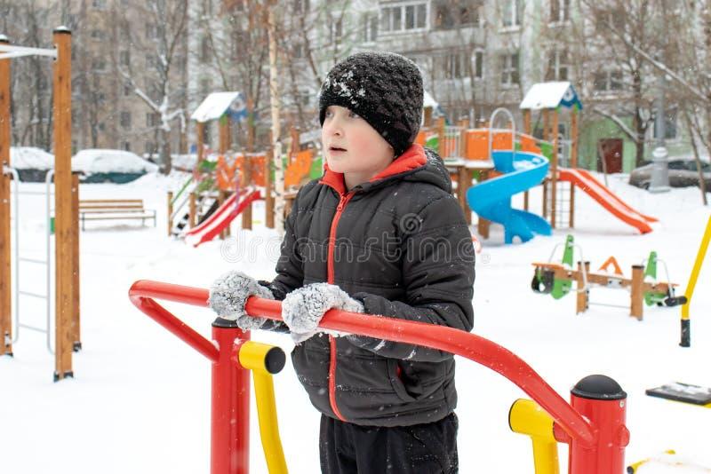 Straßentrainingsausrüstung im Winter, des im Freien in der Eignung Sports und im Bodybuilding Junge in einem Sportspielplatz, der lizenzfreie stockfotografie