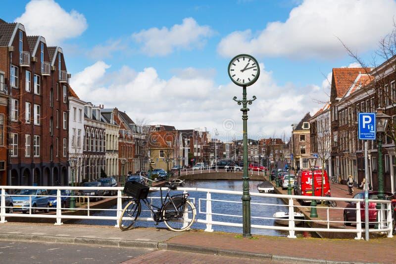 Straßenuhr, Brücke, Fahrrad, traditionelle Häuser, Kanal in Leiden, die Niederlande lizenzfreies stockbild