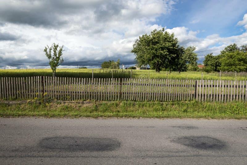 Straßenzaun, Wiese mit Bäumen und Wolken lizenzfreies stockfoto