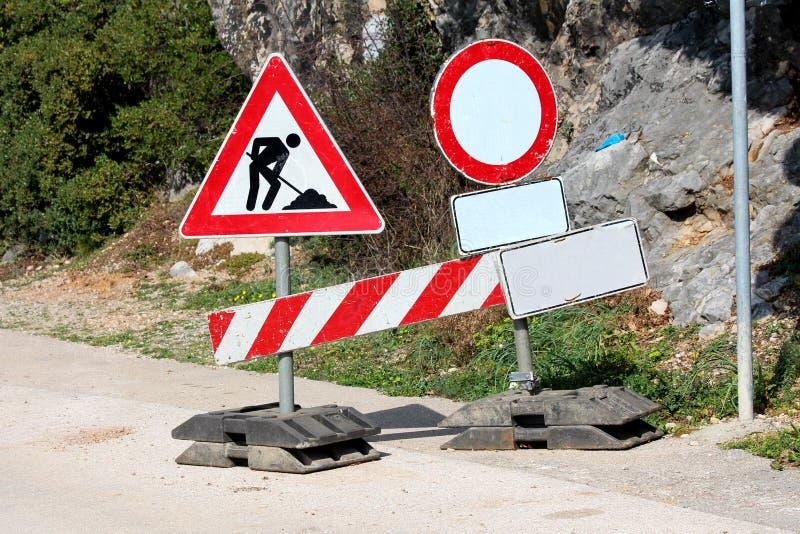 Straße schloss die im Bau Metallverkehrsschilder, die an den Plastikhaltern auf gepflasterter Straße mit Felsen und Bäumen in Rüc stockbild