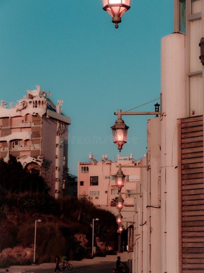 Straßenansicht an der Dämmerung im Tel Aviv-Buchtbereich mit warmen klaren Farben von Sommer- und Straßenlaterne an, nach Sonnenu stockfotografie