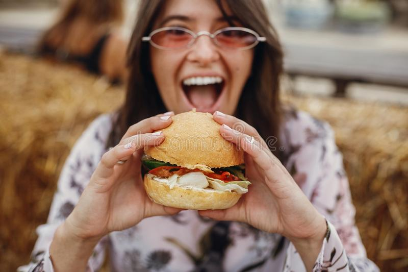 Straßenlebensmittelfestival Stilvolles Hippie-Mädchen in der Sonnenbrille köstlichen Burger des strengen Vegetariers am Straßenna stockbild