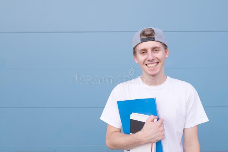 Straßenporträt eines jungen Mannes mit Büchern auf dem Hintergrund einer blauen Wand stockfotografie