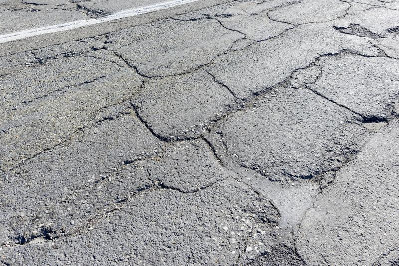 Frost damage after winter. Asphalt after winter looks like this one - cracked, loose, with little stones all over - soon, there will be bigger potholes in the stock image