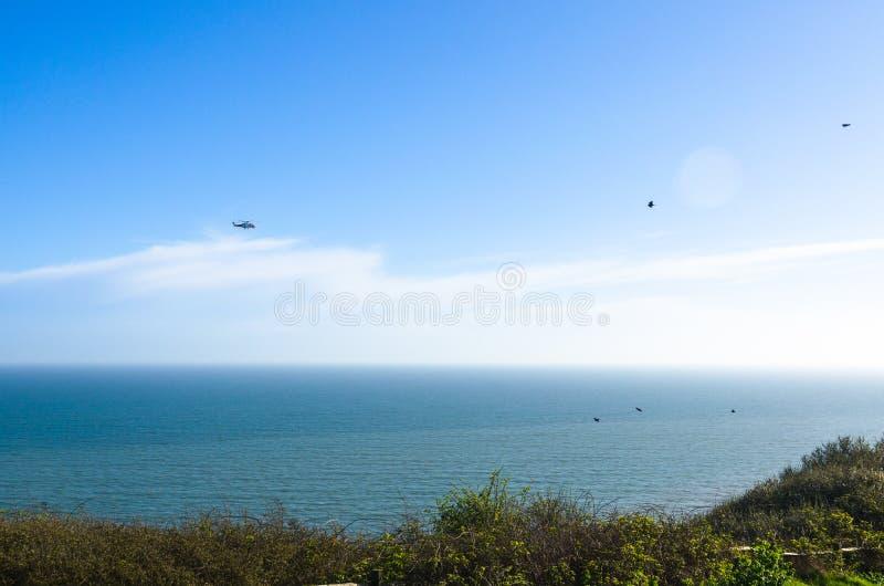 Straż wybrzeża helikopter i kierdel ptaki morzem zdjęcie stock