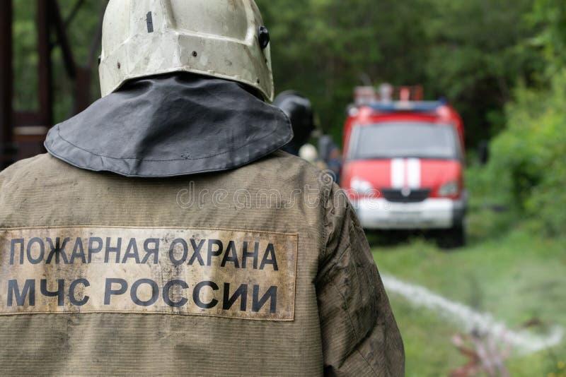 Strażacy Federacyjna Pożarnicza usługa, tylny widok z emblematem Emercom Rosja na jednolitych ratownikach obraz stock