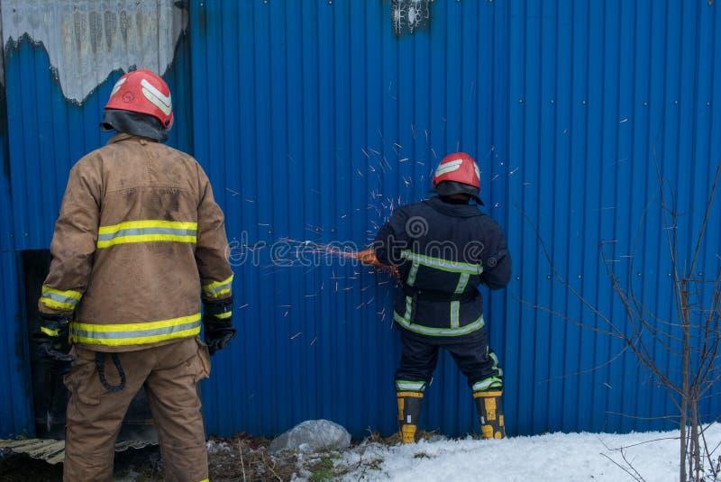 Strażacy pracują na ogieniu budynek używać metalu krajacza ratuneku narzędzie podczas ogienia Ogień gasi fotografia royalty free