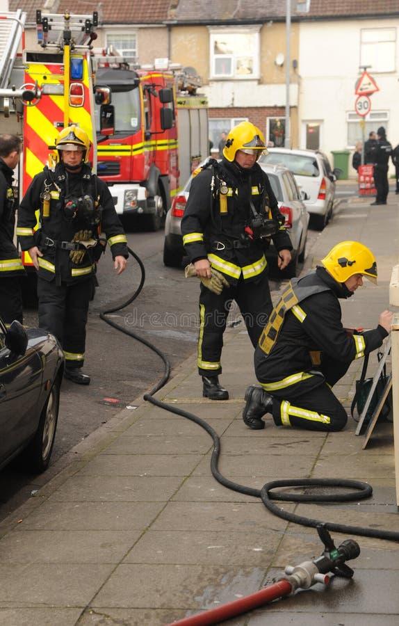 Strażacy przy domu ogieniem obrazy stock