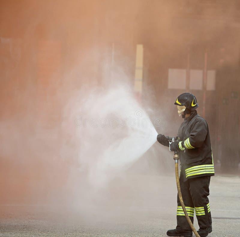 Strażak gasi wielkiego ogienia zdjęcie stock