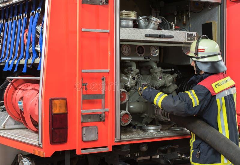 Strażak w akci i łączący pożarniczy wąż elastyczny na samochodzie strażackim obrazy royalty free