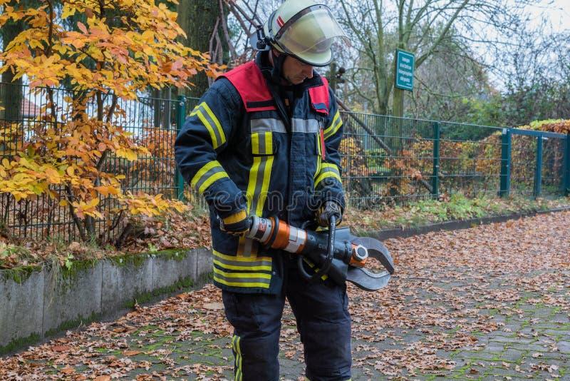 Strażak w akci z przeciwawaryjnymi narzędziami obraz stock