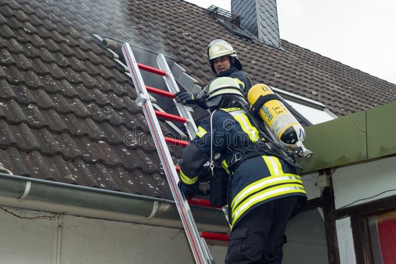 Strażak w akcji i gasi mieszkanie ogienia - Seria strażak obrazy stock