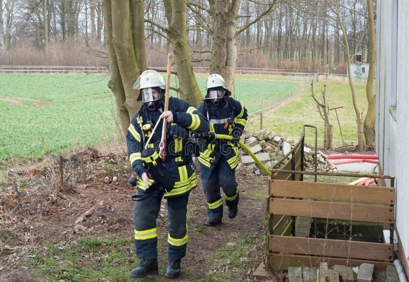 Strażak w akcji i gasi z pożarniczym wężem elastycznym - Seria strażak zdjęcie royalty free