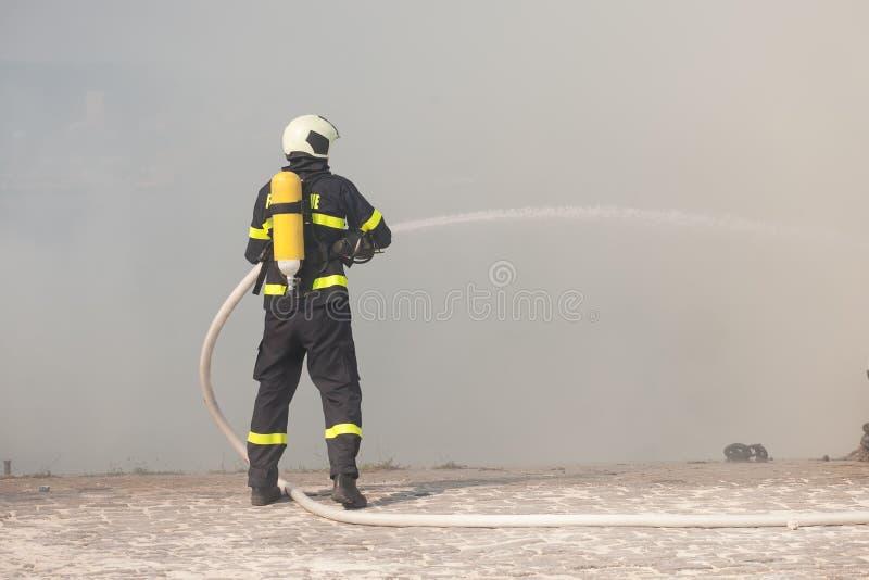Strażak w ochronnym kostiumu pracuje z wodnym wężem elastycznym Walczyć dla pożarniczego ataka fotografia royalty free