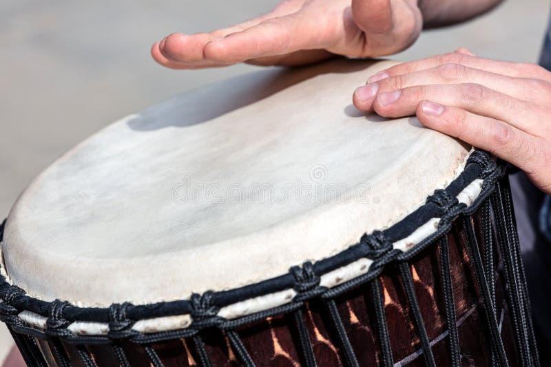 Straat begaafde musicus die Afrikaanse trommel in openlucht spelen djembe stock fotografie