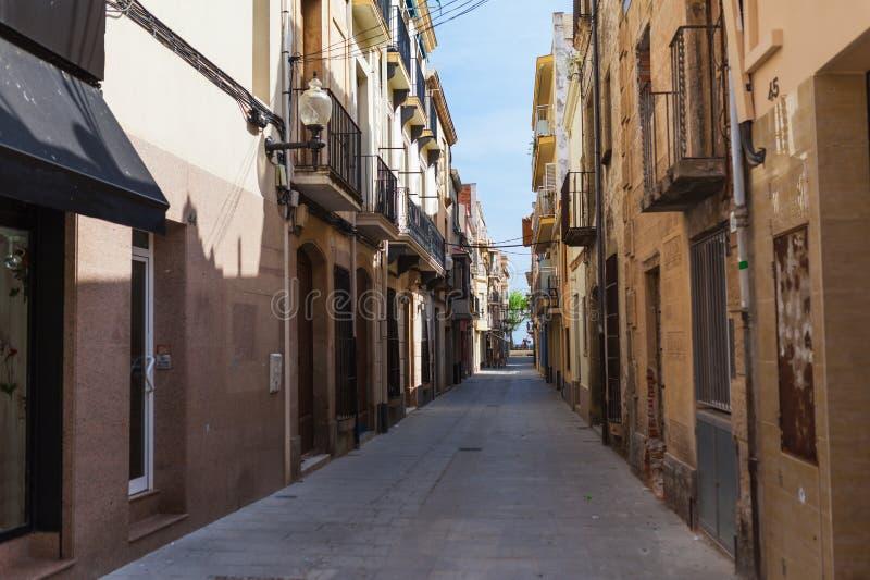 Straat in Calella in Catalonië, Spanje dichtbij Barcelona Toneel oude stad met zandstrand en duidelijk blauw water Beroemde toeri royalty-vrije stock afbeeldingen