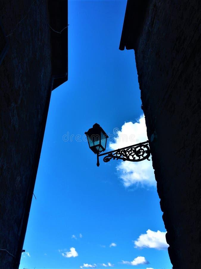 Straat in de hemel, de lamp, de muur en de wolken stock fotografie