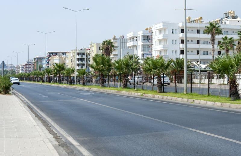 Straat in de Turkse kuststad van Mahmutlar, weg, bomen, gebouwen royalty-vrije stock afbeeldingen