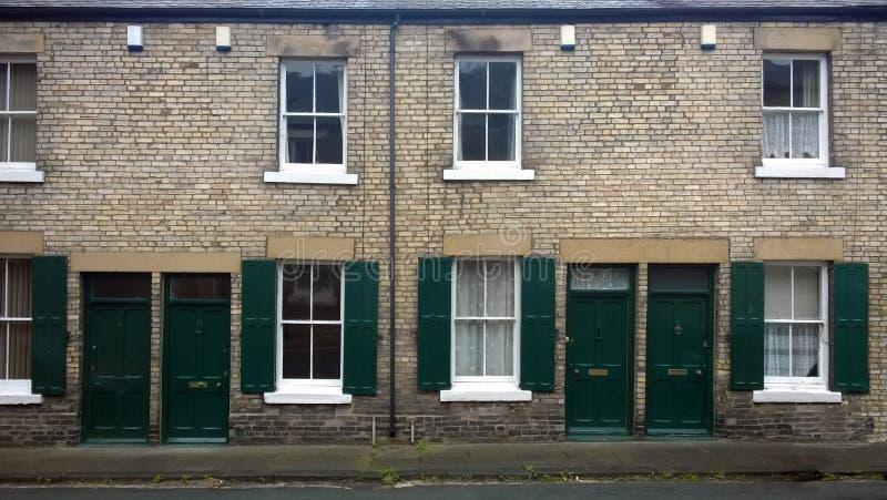 Straat met een rij van typische Britse oude terrasvormige huizen met groene deuren en vensterblinden in Durham Engeland royalty-vrije stock foto