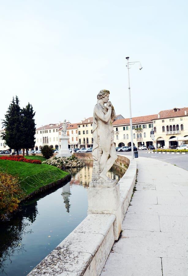 Straat, rivier, gebouwen, standbeelden, bomenkasteel in Castelfranco Veneto, in Italië stock afbeelding