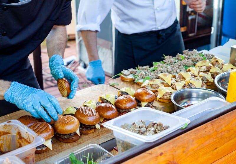 Straat snel voedsel De koks bereiden in openlucht verschillende burgers in voor royalty-vrije stock afbeeldingen