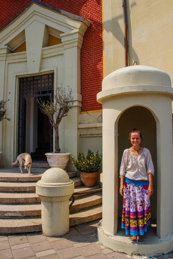 Straat van de hoofdstad van Albanië, Tirana en een jonge meisjestoerist in een fel rok lachen in een hokje bij een gebouw in de s royalty-vrije stock fotografie