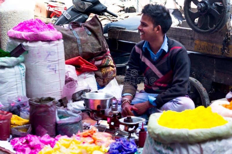 Straat zijdieverkoper met gulaal kleuren voor holi wordt omringd royalty-vrije stock afbeelding