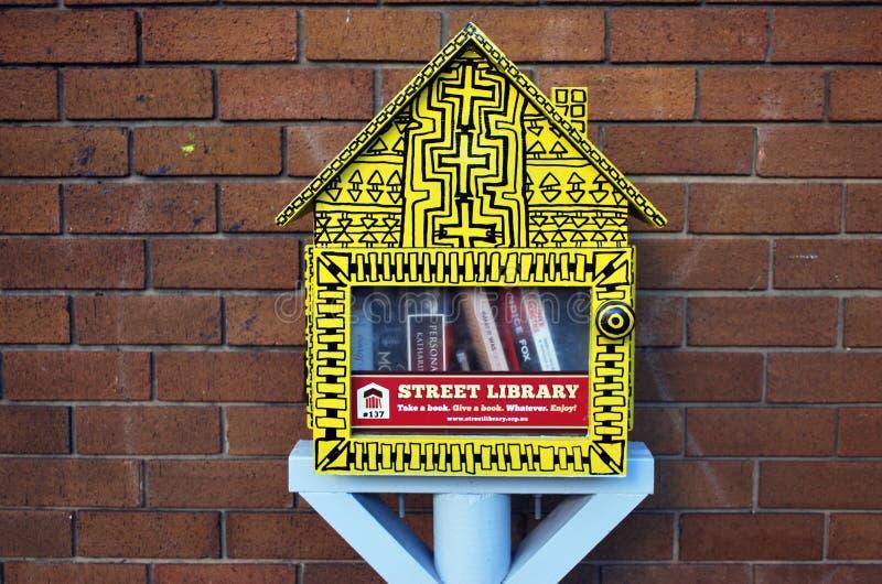 Straatbibliotheek in de vorm van een weinig gele cabine met vrije boeken Horizontaal schot van een bibliotheekuitwisseling stock afbeeldingen