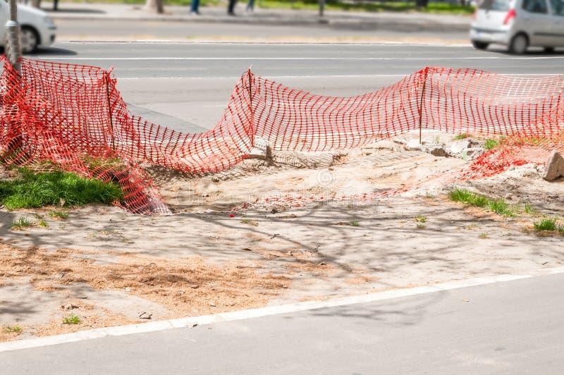 Straatbouwwerf met oranje veiligheidsnet of barrière stock afbeeldingen