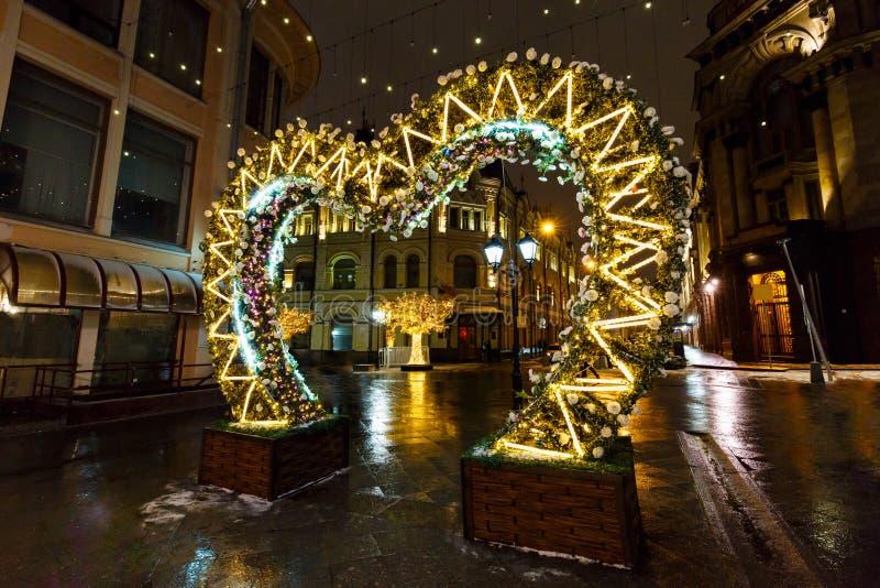 Straatdecoratie met Kerstmislichten en Verlichte bomen bij de winternacht Stad door Kerstmis en Nieuwjaarvakantie wordt verfraaid royalty-vrije stock foto's