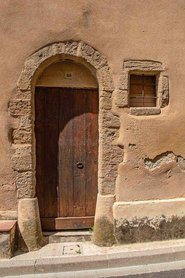 Straatdeur van hout op oude steenmuur wordt gemaakt in châteauneuf-du-Pape die royalty-vrije stock foto