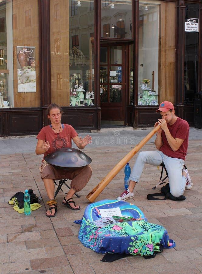 Straatfotografie - twee musici het spelen hangt trommel en didgeridoo in Bratislava stock afbeeldingen