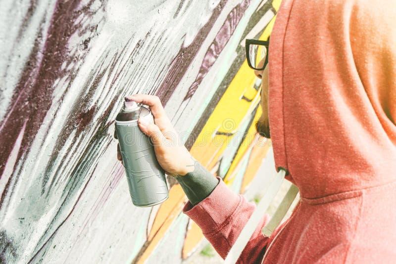 Straatkunstenaar het schilderen graffiti met kleurennevel zijn kunst op de muur - Jonge mens die en murales op de straat schrijve stock foto's