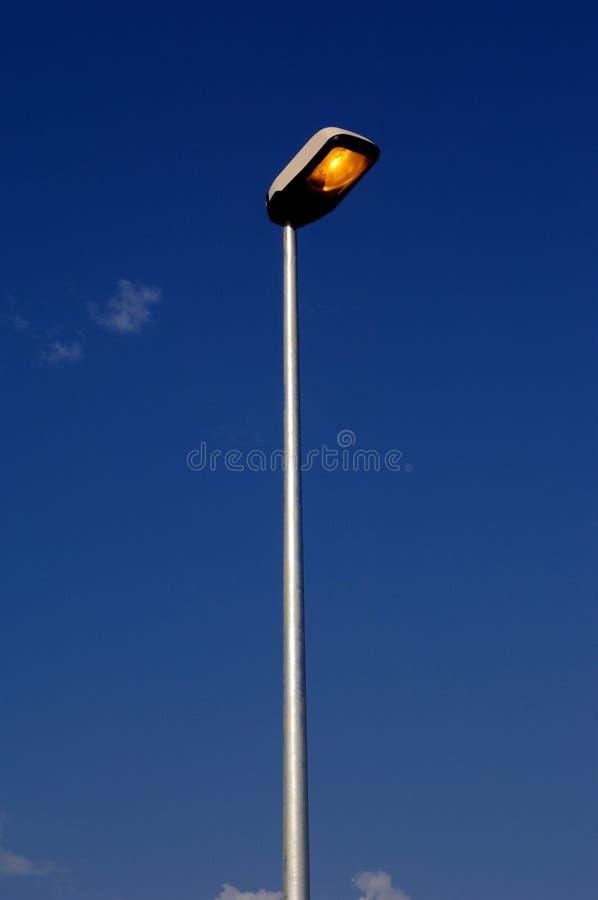 Straatlantaarn, een aangestoken straatlantaarn, met blauwe hemel royalty-vrije stock foto