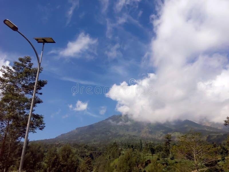Straatlantaarn en witte mooie wolk boven de berg stock afbeelding