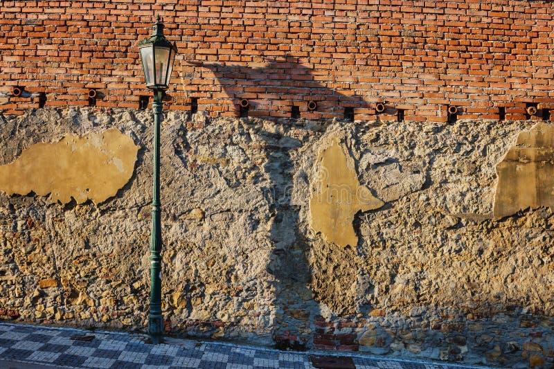 Straatlantaarn met schaduw op de achtergrond van gebroken bakstenen muur royalty-vrije stock afbeelding