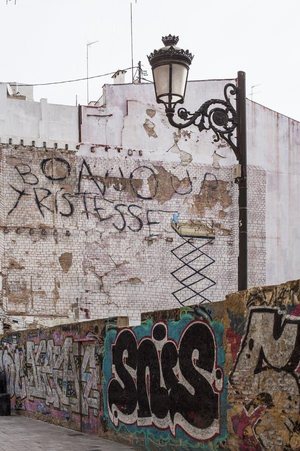 Straatlantaarn op vuile straat met graffiti stock foto