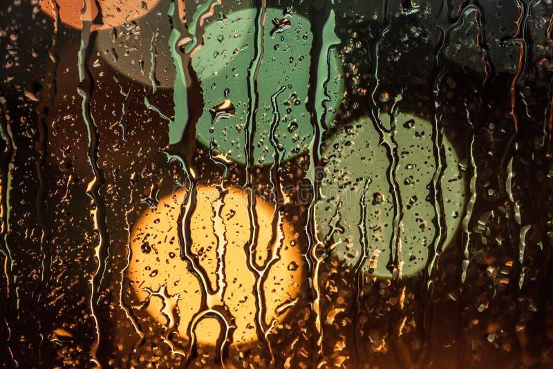 Straatlantaarns door regenachtig venster worden gezien dat royalty-vrije stock afbeeldingen