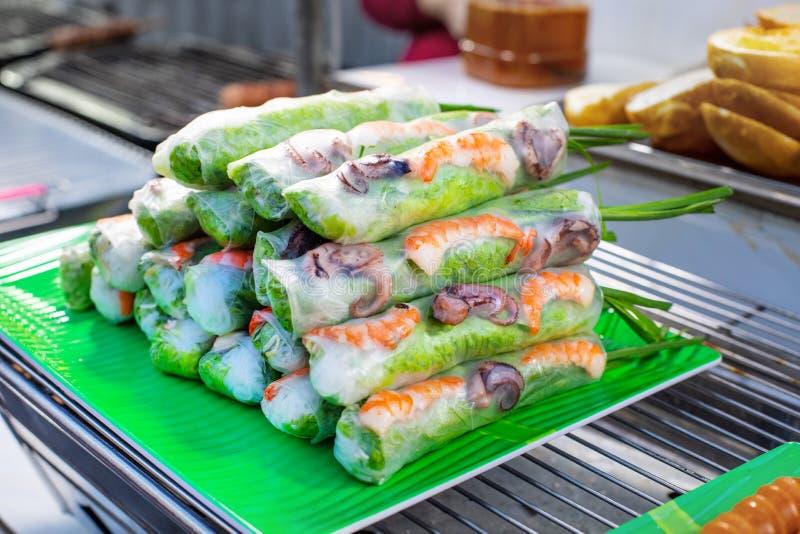 Straatmarkt met Vietnamese voedsel en cousine De lentebroodjes met zeevruchten en groenten stock foto