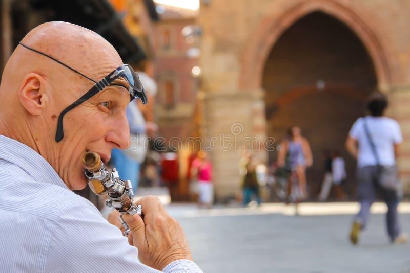 Straatmusicus die de fluit op Piazza Maggiore in Bologna spelen royalty-vrije stock afbeeldingen
