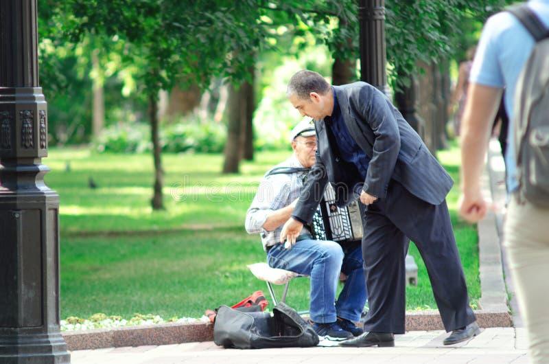 Straatmusicus die om uitvoeren de straten - Mensen het luisteren mens het spelen harmonika en het geven van klusje royalty-vrije stock foto