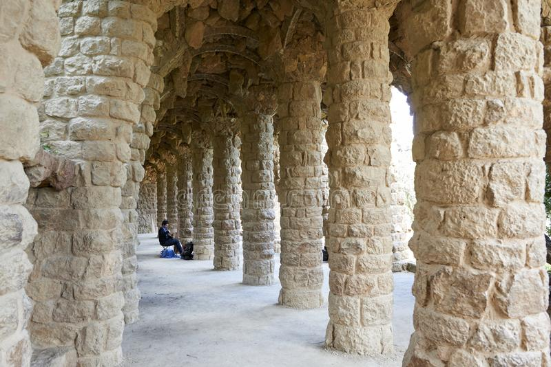 Straatmusicus in het binnenstee gedeelte van bogen met steenkolommen wordt van een Guell-Parkvoetgangersbrug, door het Spaans wor stock foto