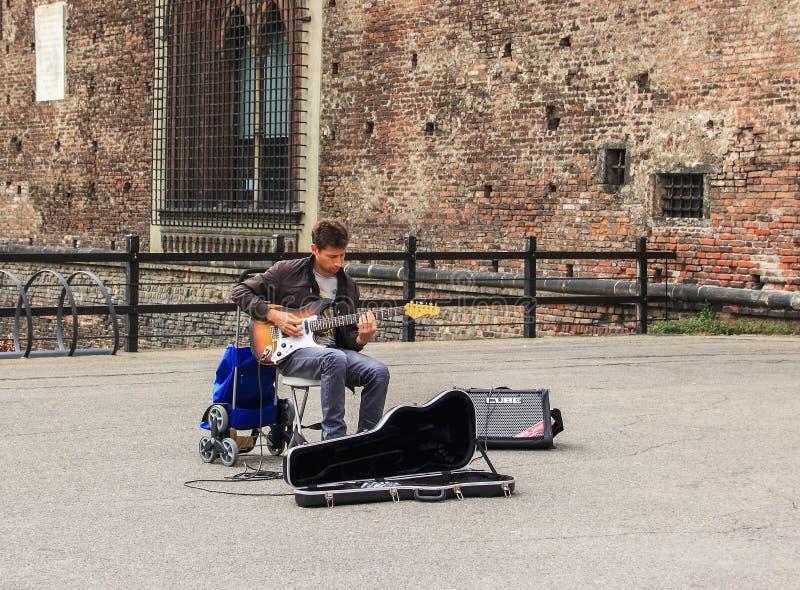 Straatmusicus het spelen gitaar bij de ingang aan Castello Sforzesco stock afbeeldingen
