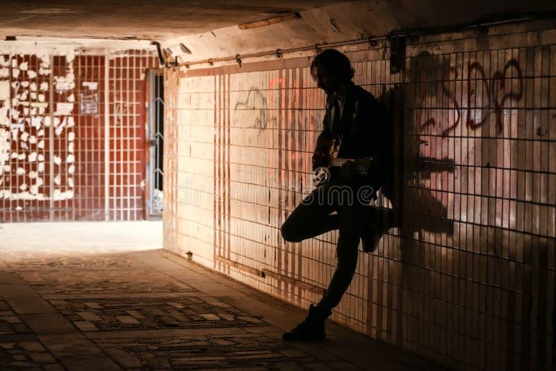 Straatmusicus het spelen gitaar in de onderdoorgang Silhouetfoto Zwerverlevensstijl Het spelen om geld het leven te maken werkloz stock foto