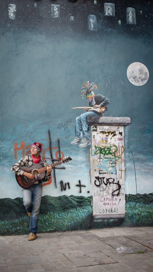 Straatmusicus vooraan een muurschildering van de gitarenspeler royalty-vrije stock afbeelding
